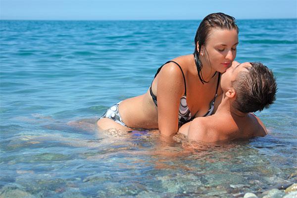Прекрасный секс в воде на морском пляже.